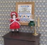 A tiny doll's house doll's doll, complete with her pleated bonnet, standing next to the 'Count Your Blessings' sampler