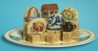Tiny tea cosies, stitched on 32 count silk gauze. Kits available from www.janetgranger.co.uk